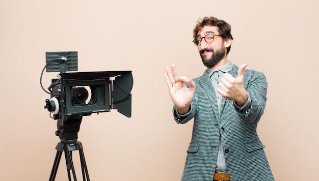 Presentador de televisión que se siente feliz, asombrado, satisfecho y sorprendido, mostrando gestos de aprobación y pulgar hacia arriba, sonriendo