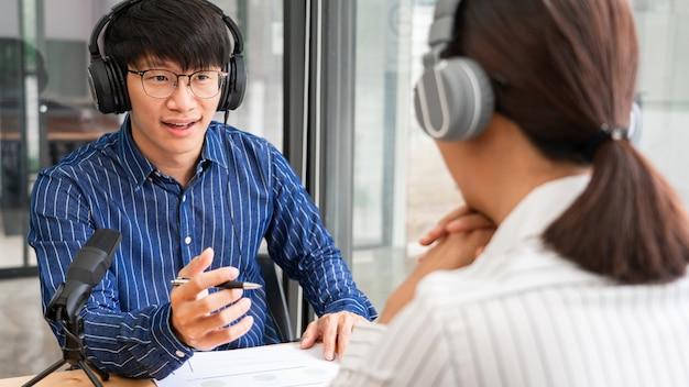 Presentadoras de radio de mujer asiática gesticulando hacia el micrófono mientras entrevistan a un hombre invitado en un estudio mientras graban juntos un podcast para un programa en línea en el estudio.