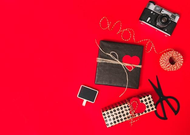 Presentar cajas con adorno de corazones, cámara fotográfica, tijeras y tableta.