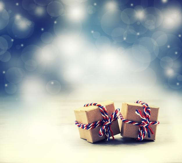 Presentar cajas atadas con cordeles de tres colores con fondo ilustrado.