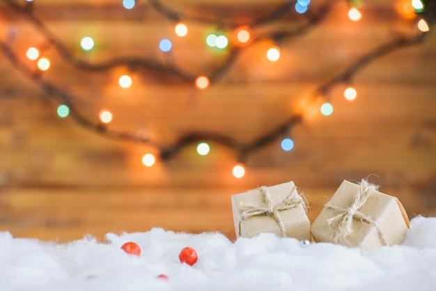 Presentar cajas en nieve decorativa cerca de luces de hadas