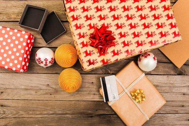 Presentar cajas en papel artesanal cerca de tarjeta plástica y bolas navideñas.