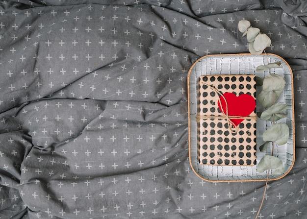 Presente caja con adorno corazón y planta ramita en bandeja.