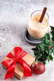 Presente la caja con cintas rojas, bolas, rompope y ramas de acebo en la mesa de piedra, copyspace plano. navidad y año nuevo