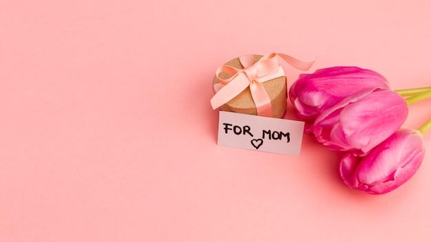 Presente caja con lazo cerca de nota y flores.