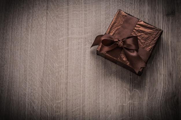 Presente en caja en papel arrugado brillante con concepto de celebración de arco