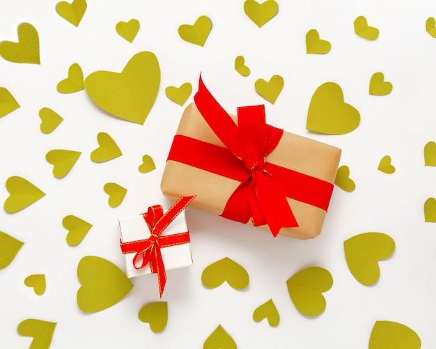 Presente caja de regalo plana. vista superior decoraciones del día de san valentín. caja de regalo, cinta roja, corazones. cumpleaños