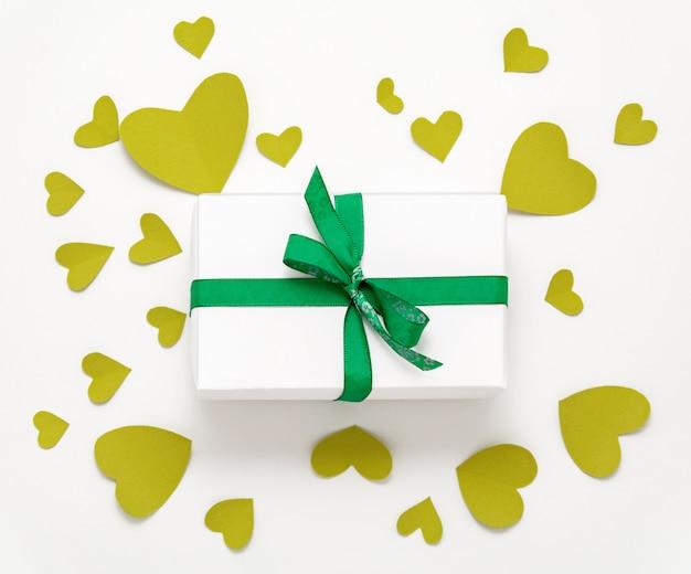 Presente caja de regalo plana. vista superior decoraciones del día de san valentín. caja de regalo, cinta verde, corazones. cumpleaños