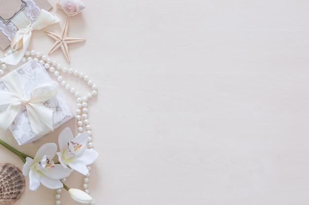 Presente, cuentas, conchas marinas, orquídeas y copyspace