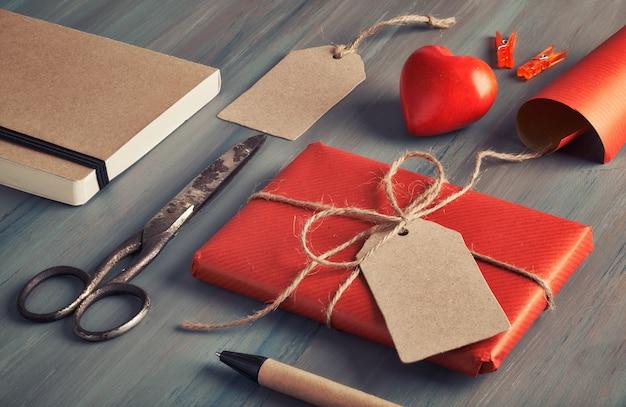 Presente empaquetado, papel de regalo, etiquetas y decoraciones en la mesa de madera rústica