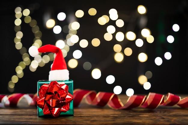 Presente y gorro navideño junto a luces de guirnalda y cinta.