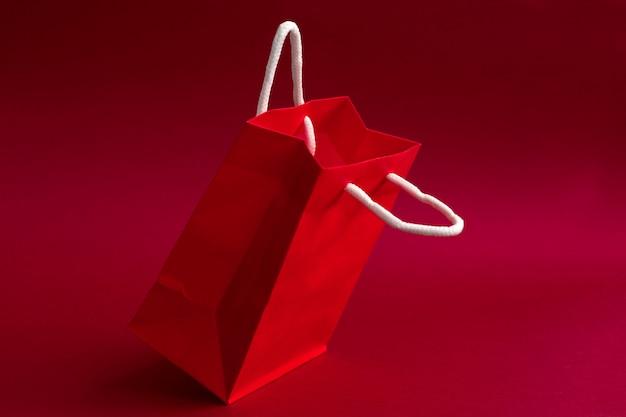 Presente rojo o bolsa de compras levitando sobre un fondo rojo.