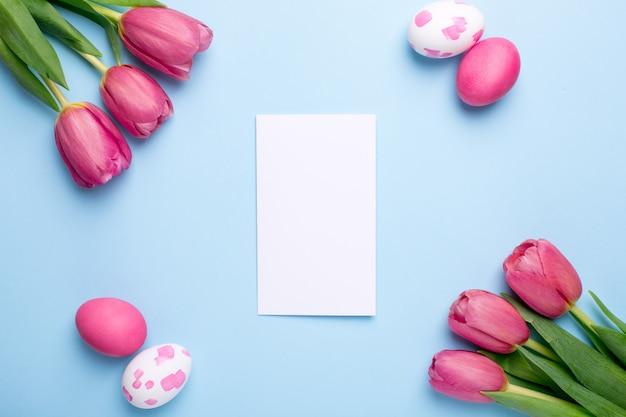 Presente tarjeta, flores tulipanes y huevos de pascua en una superficie azul