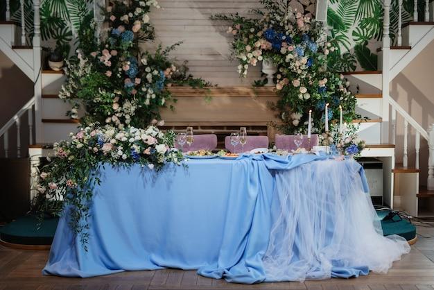 El presidium de los recién casados en el salón de banquetes del restaurante está decorado con velas y plantas verdes, glicinas cuelga del techo.