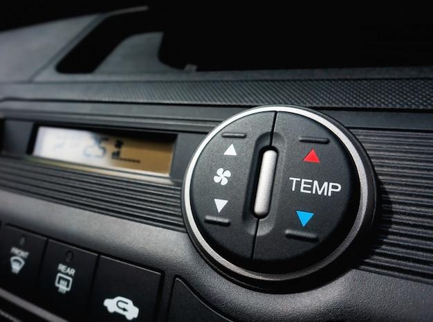 Presionando el interruptor del ventilador de un sistema de aire acondicionado de coche