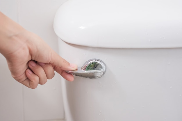Presione a mano y descargue el inodoro. concepto de limpieza, estilo de vida e higiene personal.