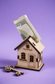 Préstamo o ahorro para comprar una casa y bienes inmuebles. documento de carga de hipoteca y calculadora de propiedad. casa de madera se encuentra con llave y dólares.