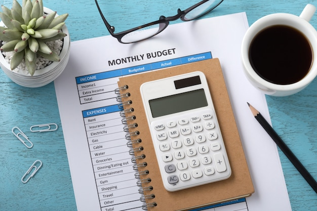 Presupuesto mensual con calculadora blanca sobre tabla azul.