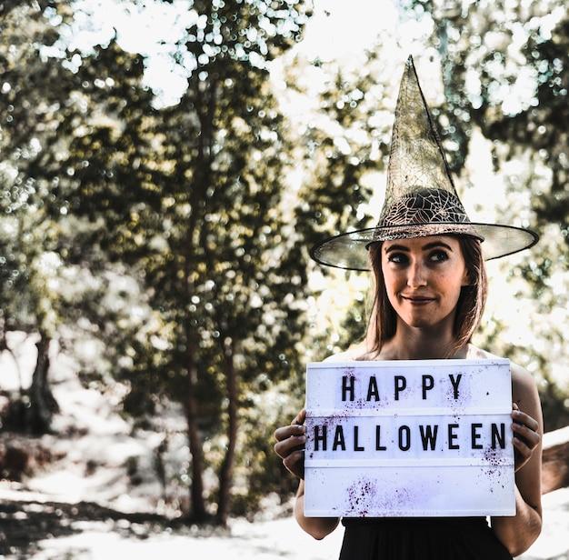 Pretty bruja con letrero de saludo en el bosque soleado