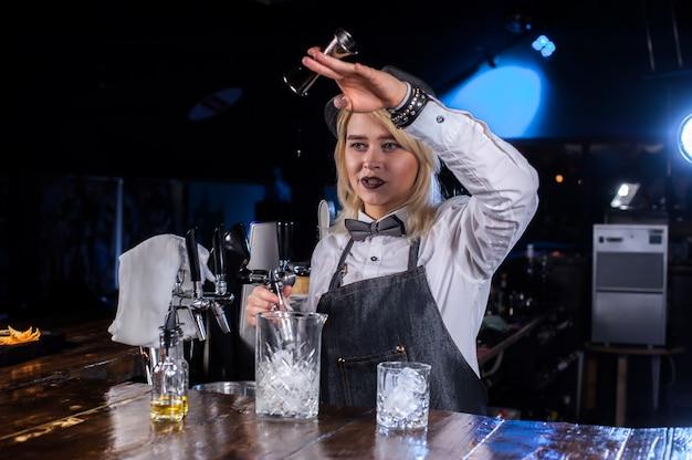 Pretty girl barman termina intensamente su creación mientras está de pie cerca de la barra del bar en el bar