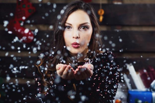 Pretty girl sopla nieve de sus palmas de pie en la sala preparada para las vacaciones de navidad