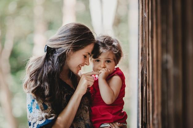 Pretty little child tiene el dedo de la madre sentado en sus brazos