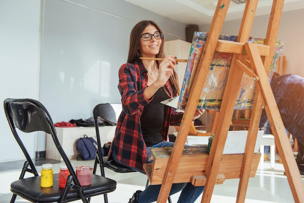 Pretty pretty girl artista pinta sobre lienzo de pintura en el caballete.
