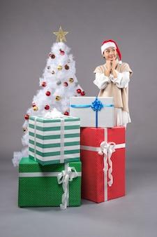 Pretty woman alrededor de regalos de navidad en gris