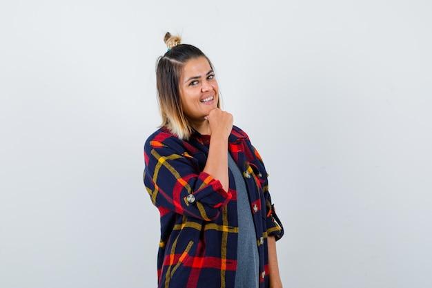 Pretty woman apoyando la barbilla en la mano con ropa casual y con un aspecto alegre.