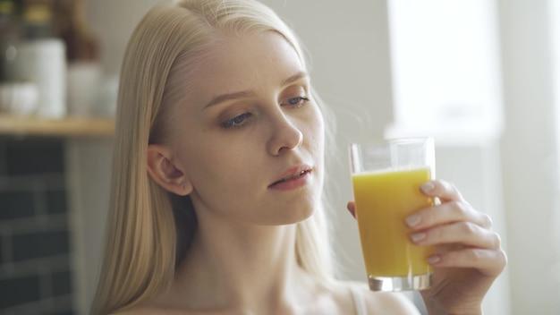 Pretty woman bebe jugo y sonríe a la cámara en la cocina. de cerca. lentamente en 4k.