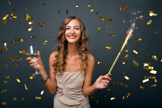 Pretty woman celebrando el año nuevo en confeti dorado