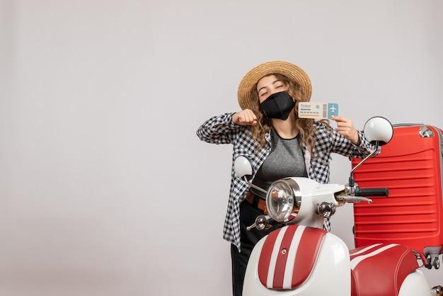 Pretty woman cerrando los ojos sosteniendo el boleto de pie cerca de la maleta roja del ciclomotor
