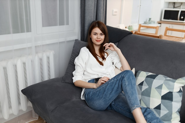 Pretty woman se encuentra en un sofá con almohadas en un apartamento confort.