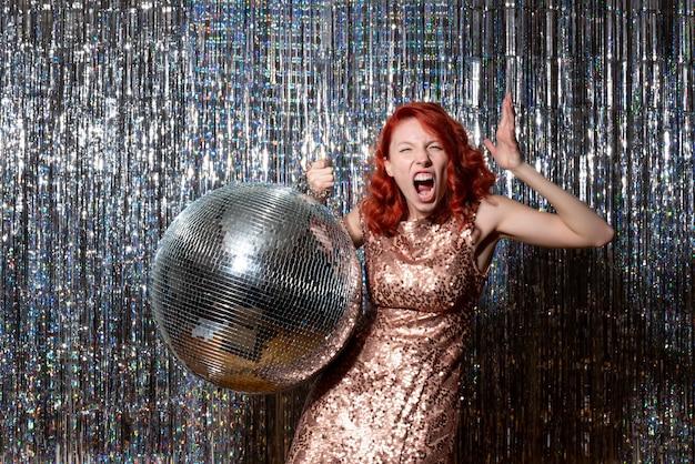 Pretty woman en una fiesta disco gritando airadamente en cortinas brillantes