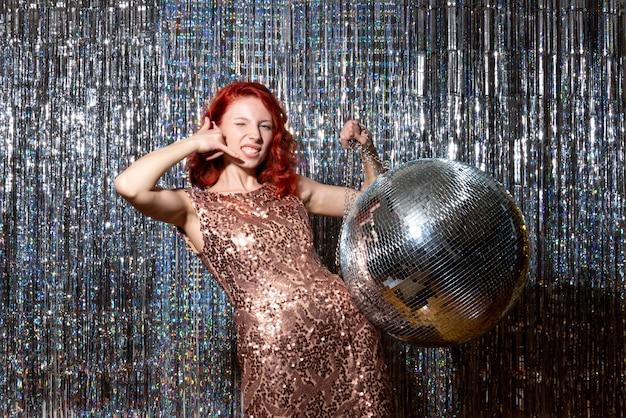 Pretty woman en fiesta disco posando en cortinas brillantes