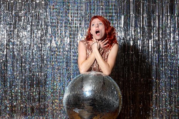 Pretty woman en la fiesta de discoteca con problemas para respirar en cortinas brillantes