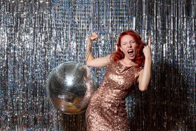 Pretty woman en fiesta de discoteca regocijándose en cortinas brillantes