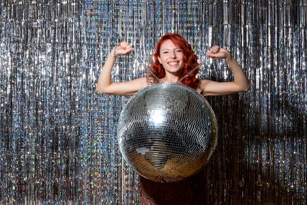 Pretty woman en la fiesta de discoteca regocijándose sonriendo en cortinas brillantes