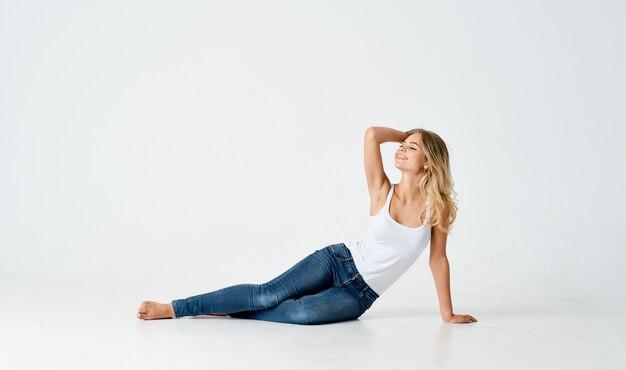 Pretty woman se sienta en el piso claro, inclinada hacia un lado en pleno crecimiento