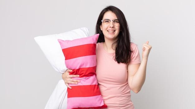 Pretty woman sintiéndose conmocionada, riendo y celebrando el éxito vistiendo pijama y sosteniendo una almohada