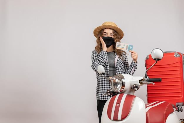 Pretty woman sosteniendo el boleto de pie cerca de la maleta roja del ciclomotor en ciclomotor