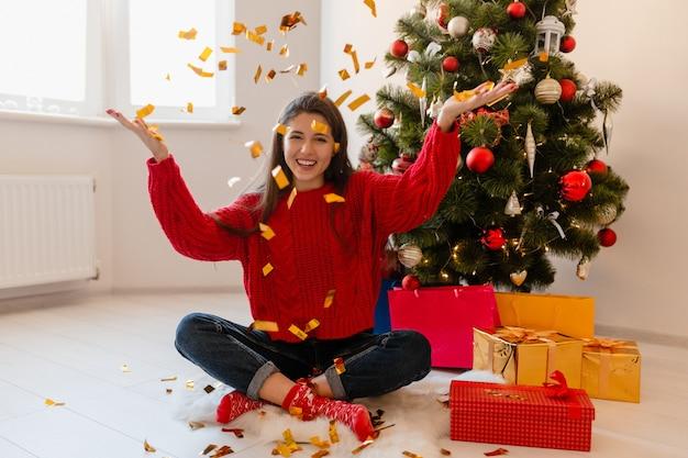 Pretty woman en suéter rojo sentado en casa en el árbol de navidad lanzando confeti dorado rodeado de regalos y cajas de regalo