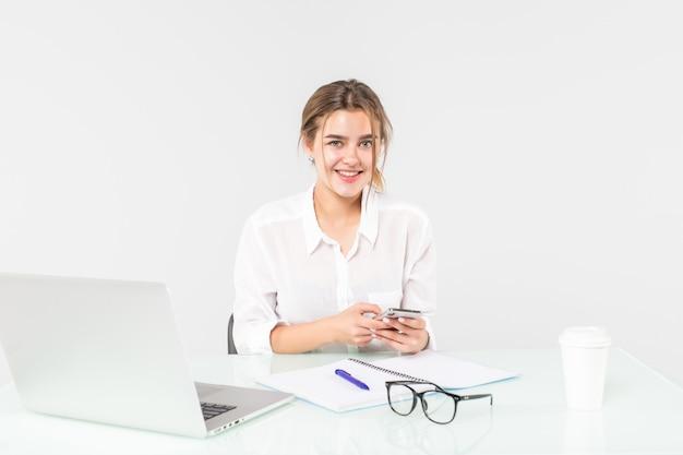 Pretty woman está trabajando en una computadora portátil y leyendo un mensaje en su teléfono aislado sobre fondo blanco.