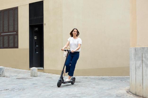 Pretty woman usando un scooter ecológico