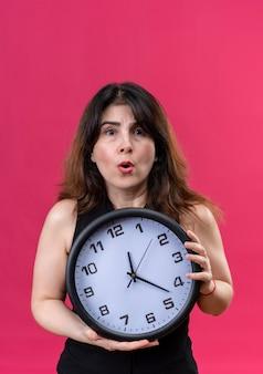 Pretty woman vistiendo blusa negra asustada por llegar tarde detrás del reloj