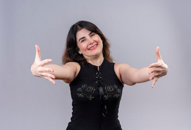 Pretty woman vistiendo blusa negra coridalmente abrazando con los brazos a la cámara rejo sobre fondo gris