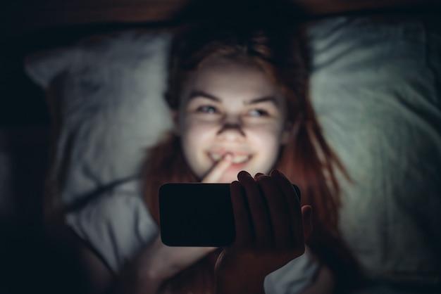 Pretty woman yace en la cama con un teléfono en sus manos en la relajación de la adicción de noche