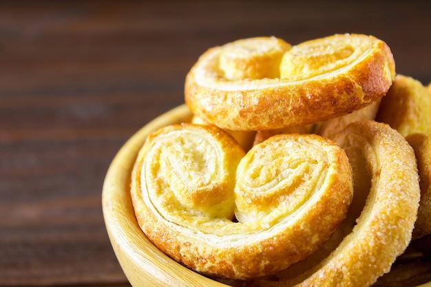 Pretzels dulces hechos de hojaldre en un recipiente en una mesa de madera