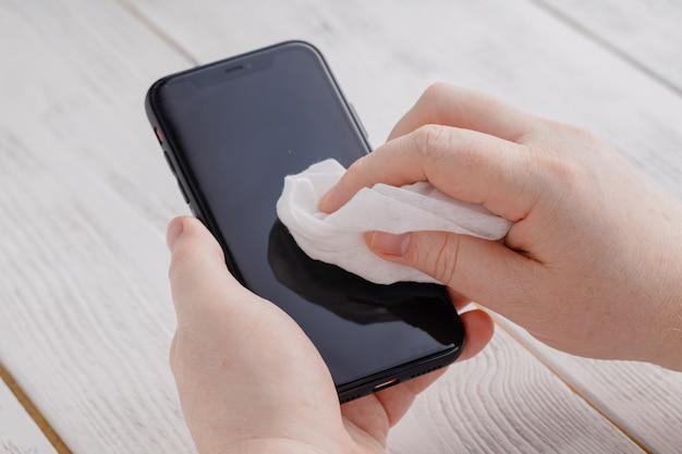 Prevención covid 19 aplicando desinfección con alcohol al teléfono móvil