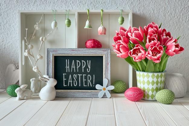 Primavera con decoraciones de pascua, tulipanes y una pizarra con texto feliz pascua